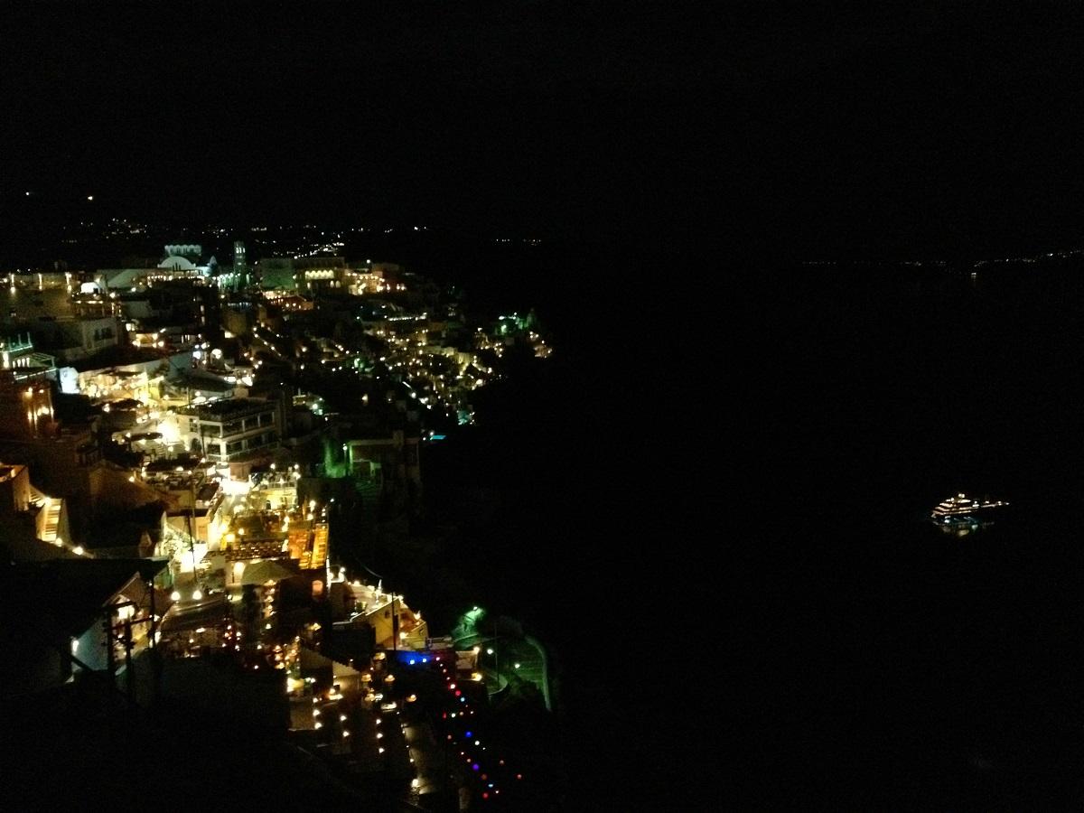 Santorini caldera towns glowing at night.